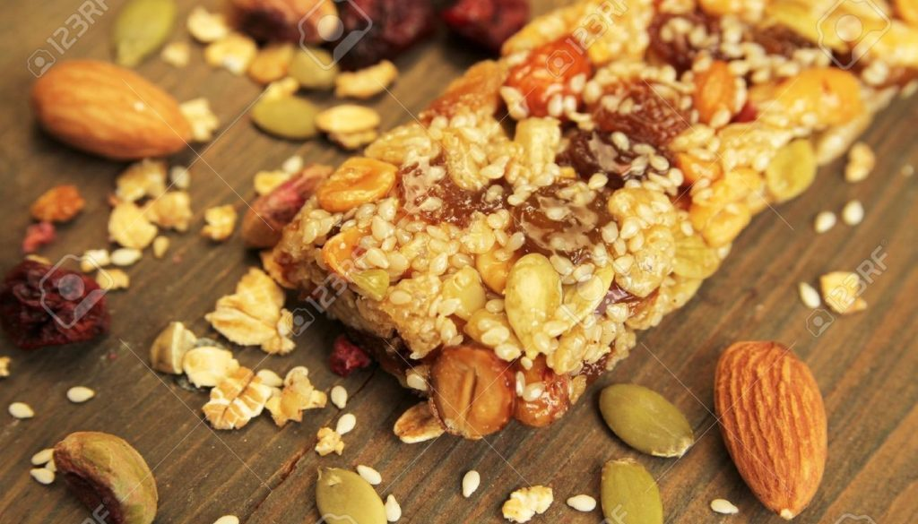 14626465 Organic granola bar with nuts and dry fruits on a wooden table Stock Photo